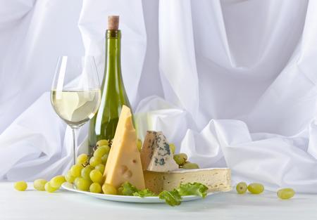 Käse mit Trauben und Wein auf weißem Tisch
