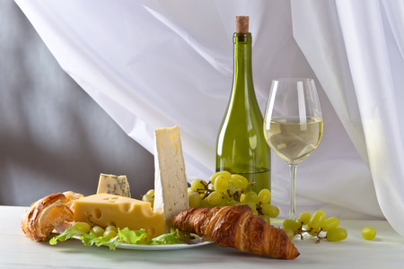 bri: various cheeses with grapes and croissants on white table