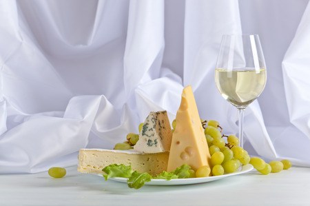 bri: cheeses with grapes and wine on white table