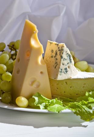 bri: various cheeses with grapes on white table Stock Photo