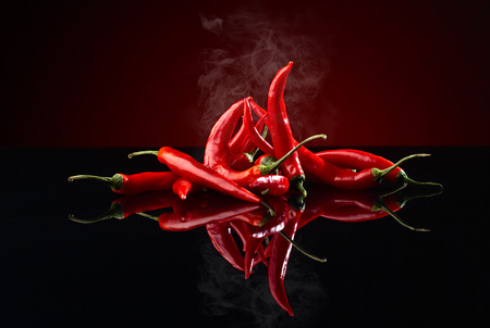 spicy chilli: beam of red chilli pepper on black background