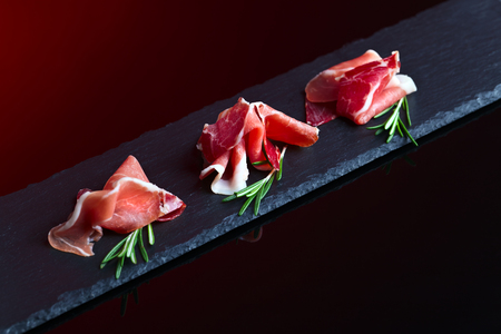jamon with rosemary on a dark background Stock Photo