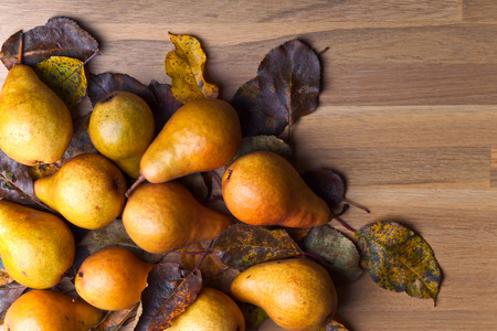 fall harvest: Juicy ripe pears with dried leaves on wooden table Stock Photo
