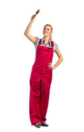 jumpsuit: Young happy woman in red jumpsuit with paint brush , isolated on white Stock Photo
