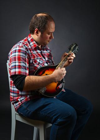 mandolin: portrait of musician with mandolin, studio shot Stock Photo