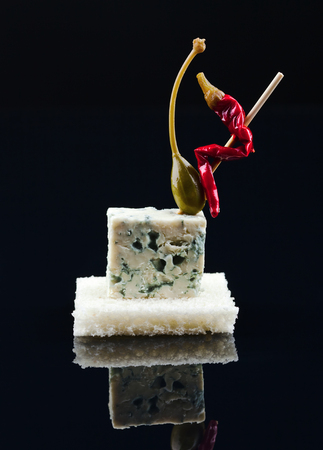 alcaparras: canned capers, pepper and Blue cheese  on a black reflective background