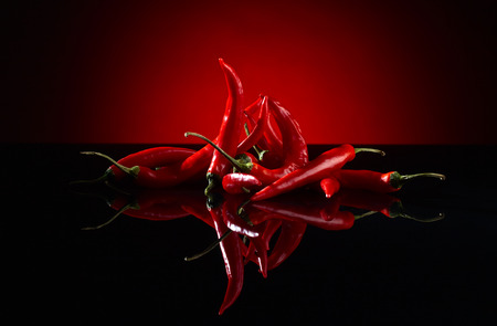 red chilli pepper plant: beam of red chilli pepper on black background
