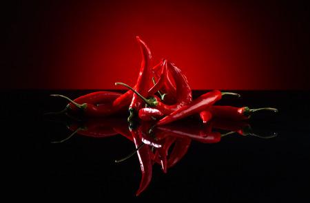 pepe nero: fascio di peperoncino rosso su sfondo nero Archivio Fotografico