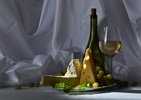 bri: cheese with grapes and wine on white table Stock Photo