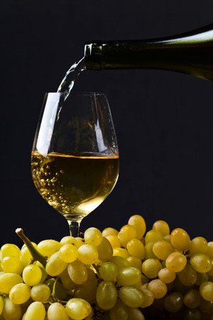 White wine being poured into a wineglass.