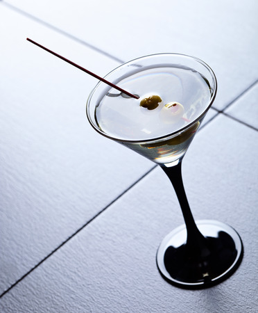 martini glasses: glass of martini, focus on a olives