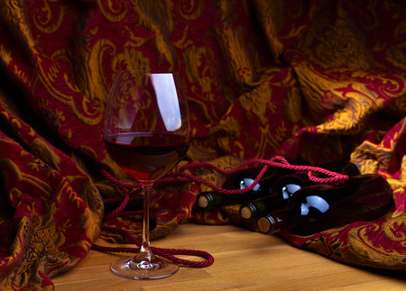 gold table cloth: bottles and glass with red wine on wooden table Stock Photo