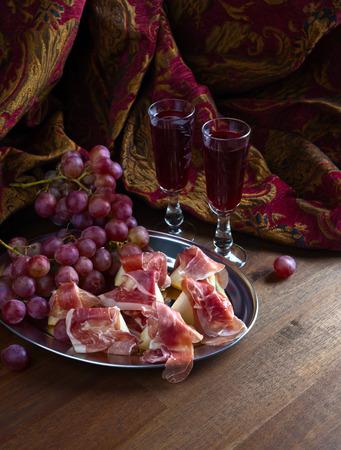 jamon espagnol avec melon et raisin sur table en bois Banque d'images