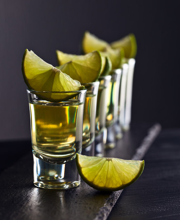 alcoholic drink: alcoholic drink with lime on dark background