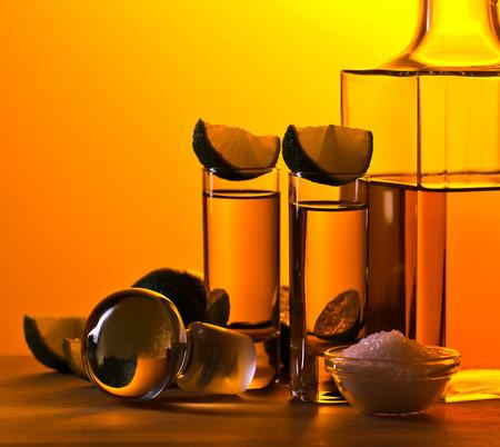 alimentos y bebidas: el tequila de oro con sal y limón en la mesa de madera