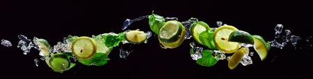 Kalk- en Citroenstukken Met Bladeren Van Pepermunt Op Zwarte Achtergrond Stockfoto