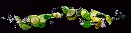 lime and lemon pieces with leaves of peppermint on black background