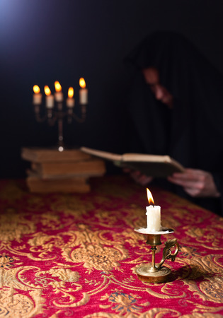 Candle in a small candlestick and reading monk