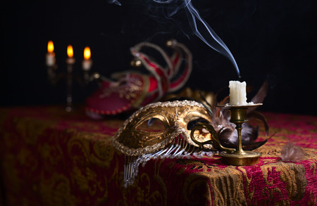 Candle in small brass candlestick and Venetian mask Stock Photo