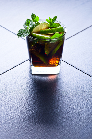 libre: cocktail Cuba libre with lime, ice and peppermint leaves