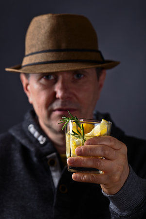focus in foreground: man with a glass of lemon drink  , focus on foreground Stock Photo