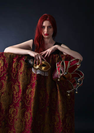 redheaded: Beautiful redheaded woman in a black dress with carnival mask