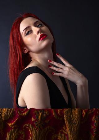 redheaded: Beautiful redheaded woman in a black dress Stock Photo