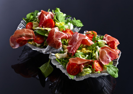 jamon: green salad with jamon on a black background Stock Photo