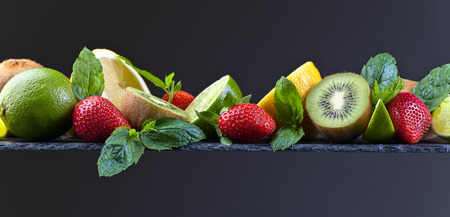 The ripe juicy fruits and peppermint leaves on a dark background Stock Photo