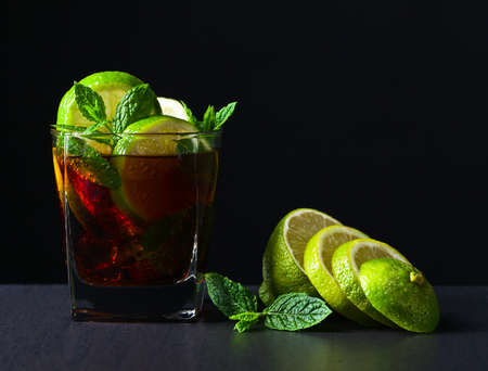 libre: cocktail Cuba libre with lime, ice  and peppermint leaves Stock Photo