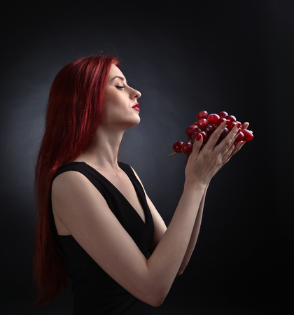 redheaded: Beautiful redheaded woman in a black dress with grape