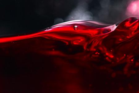 Rotwein auf schwarzem Hintergrund, abstrakte Spritzwasser.