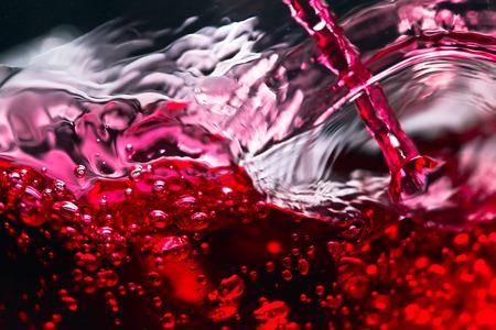 splash abstract: Red wine on black background, abstract splashing.