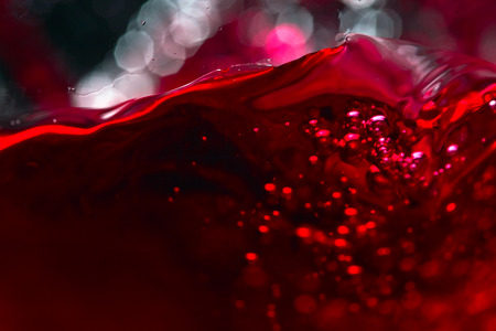 translucent red: Red wine on black background, abstract splashing.
