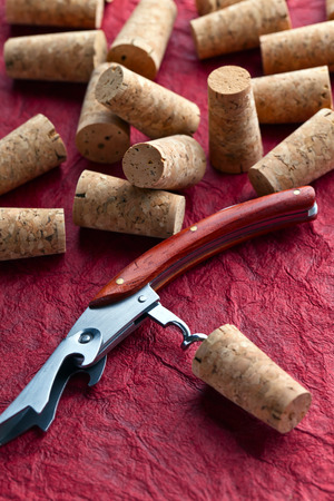 closed corks: corkscrew and corks on a red background Stock Photo