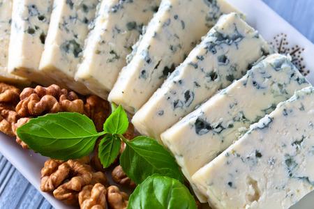 gorgonzola: gorgonzola cheese with basil and walnuts on blue table