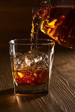 whiskey with ice on old wooden table Stock Photo