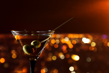 night stick: martini with green olives on a background of night city