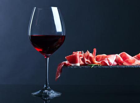 Jamon mit Rotwein und Rosmarin auf einem schwarzen Hintergrund