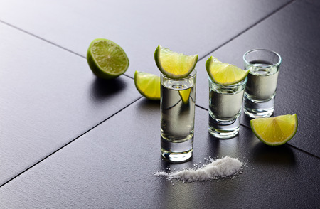 tequila: tequila , lime and salt on black table