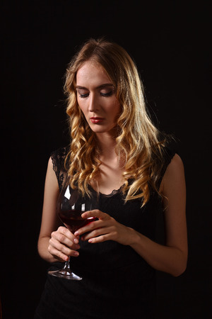 lady in red: young beautiful blonde in black dress with glass of red wine Stock Photo