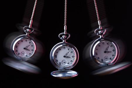 Montre de poche se balancer sur une chaîne d'hypnotiser, fond noir Banque d'images