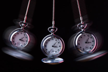 Pocket watch swinging on a chain to hypnotise , black background