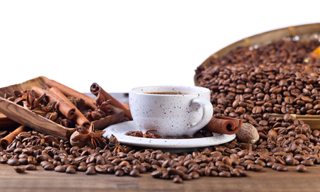 Cup of black coffee and roasted beans with spices, isolated on white