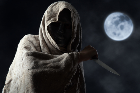 The hooded man in mask with a big knife