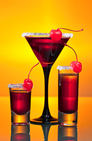 sweet vermouth: alcoholic drinks with sweet cherry on yellow background Stock Photo