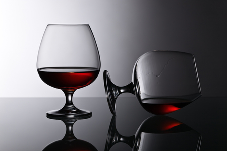 liquid reflect: Two snifters of brandy on the reflective background Stock Photo