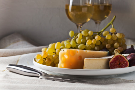 cheese with fig and grape on a white plate