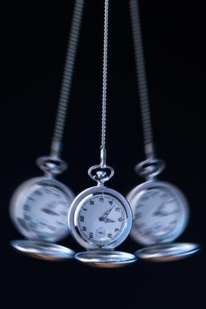 Zakhorloge op een swingende keten hypnotiseren, zwarte achtergrond Stockfoto