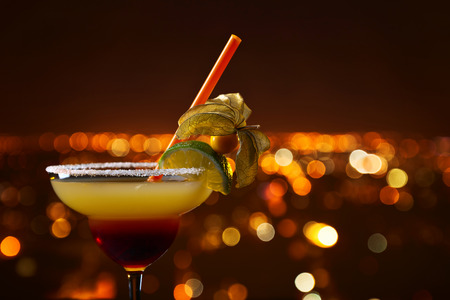 Cocktail with physalis and lime on a background of hight city Stock Photo